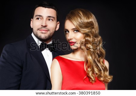Happy beautiful man and woman on the dark background - stock photo