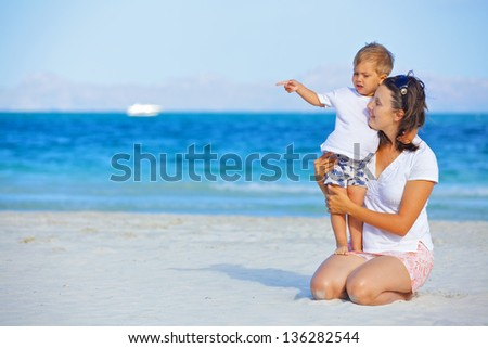 Happy beautiful mother and son enjoying beach time - stock photo