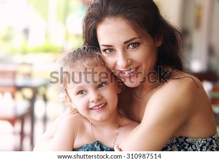 Happy beautiful mother cuddling her daughter with smile in cafe. Closeup portrait - stock photo