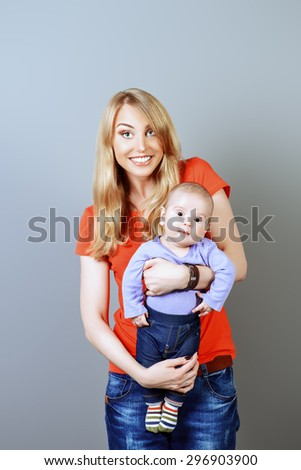 Happy beautiful mother holds her adorable baby. Family concept. Studio shot. - stock photo