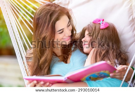 Happy beautiful mother with cute little daughter sitting on backyard in hammock and reading interesting book, family spending time together outdoors