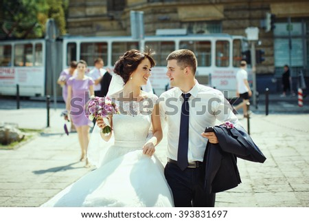 Happy beautiful newlyweds walking in old town