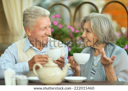 Happy beautiful older couple drink coffee together - stock photo