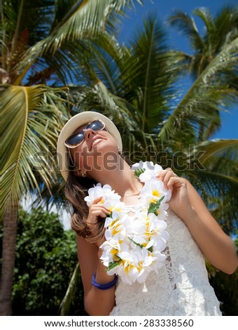 Happy beautiful people. Girl in white dress with welcoming Lei cheerful, happiness during summer vacation holidays on Hawaii. Hawaiian travel vacations in Waikiki, Honolulu city, Oahu, Hawaii, USA. - stock photo