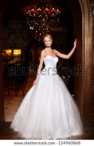 Happy beautiful sexy bride blond girl woman in white wedding dress with hairstyle and bright makeup in interior - stock photo