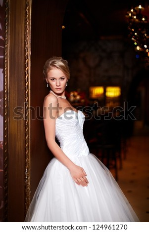 Happy beautiful sexy bride blond girl woman in white wedding dress with hairstyle and bright makeup in interior