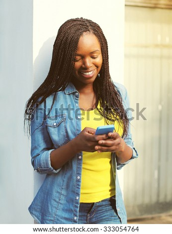 Happy beautiful smiling african woman using smartphone in city - stock photo
