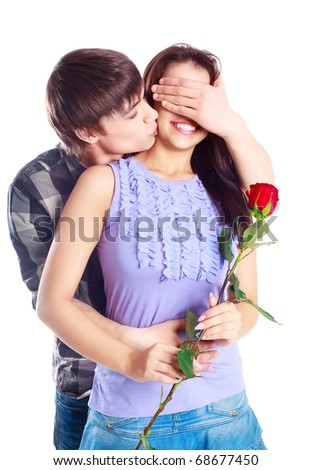 happy beautiful  teenage couple, a boy giving a rose to his girlfriend and kissing her - stock photo