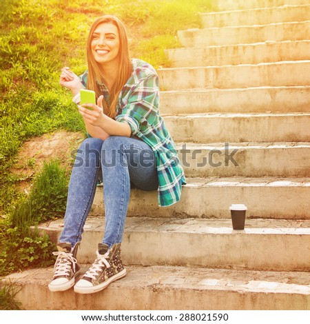 Happy beautiful teenage girl sitting on stairs in park on sunny summer day with smartphone and takeaway coffee. Square format, retouched, vibrant colors. - stock photo