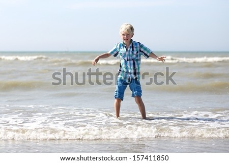 Happy beautiful teenager boy has fun playing with water at a shore of the sea on a sunny summer day - stock photo