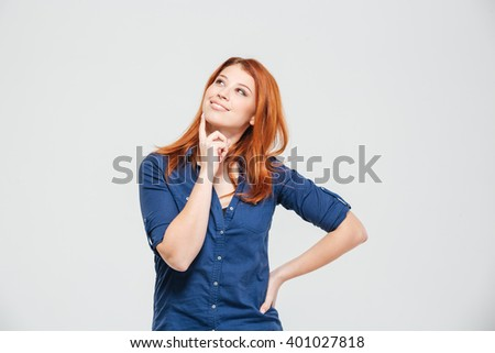 Happy beautiful thoughtful redhead young woman standing and dreaming over white background - stock photo