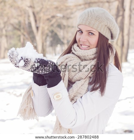 Happy Beautiful Winter Woman playing with snow in the park. Caucasian female wintertime portrait outdoor. - stock photo