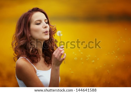 happy beautiful woman blowing dandelion in the field - stock photo
