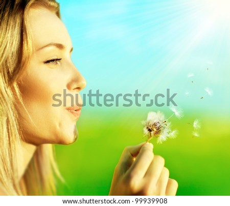 Happy beautiful woman blowing dandelion over blur background, having fun and playing outdoor, teen girl enjoying nature, summer vacation and holidays, young pretty female holding flower, wish concept - stock photo