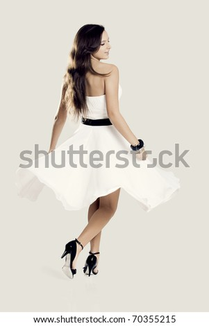Happy beautiful woman dancing and wearing a wonderful white dress - stock photo