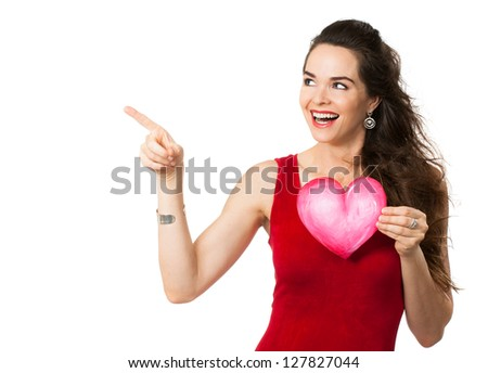 Happy beautiful woman holding a love heart and pointing at copy-space. Isolated on white. - stock photo