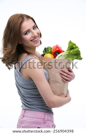 Happy beautiful woman holding a shopping bag full of groceries - stock photo