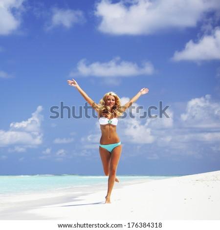 Happy beautiful woman in bikini running on the beach - stock photo