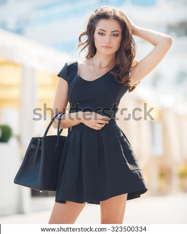 Happy beautiful woman in black summer dress walking and cheerful smiling in the city. Pretty sexy fashion model girl in her 20s. Caucasian female model outside. - stock photo