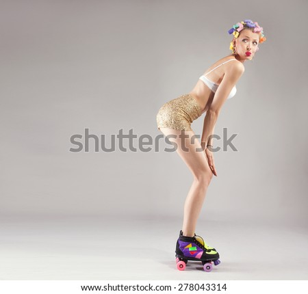 Happy beautiful woman in lingerie posing with curlers on her hair. Studio shot. - stock photo