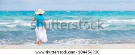 Happy beautiful woman in the beach hat looking at the sea. Panorama - stock photo