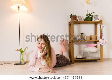 Happy beautiful woman lying on the floor in the room and talking on the phone - stock photo