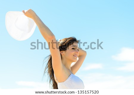 Happy beautiful woman on summer day. Girl raising arm,  holding white hat and smiling on blue copy space background. Happiness holidays. - stock photo