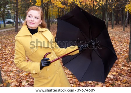Happy beautiful woman playing with her umbrella in an autumn park