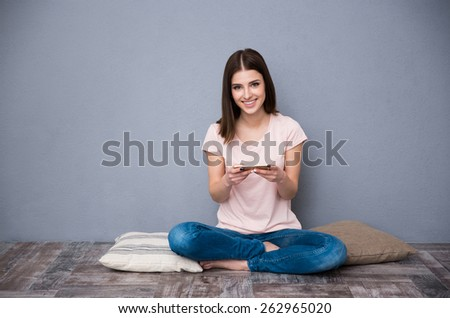 Happy beautiful woman sitting on the floor and using smartphone - stock photo