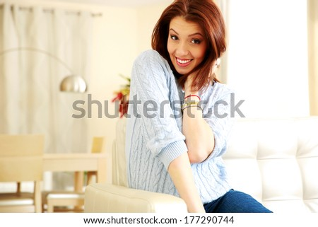 Happy beautiful woman sitting on the sofa at home