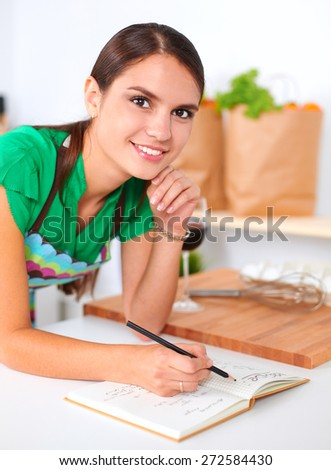 Happy beautiful woman standing in her kitchen writing on a notebook at home - stock photo