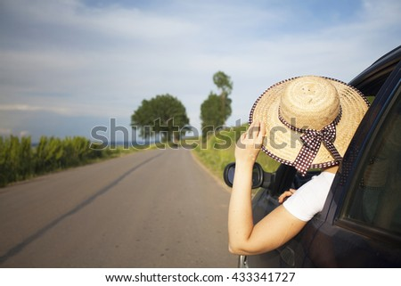 Happy beautiful woman traveling in a car across Europe. Freedom, travel and vacation road trip concept lifestyle image.