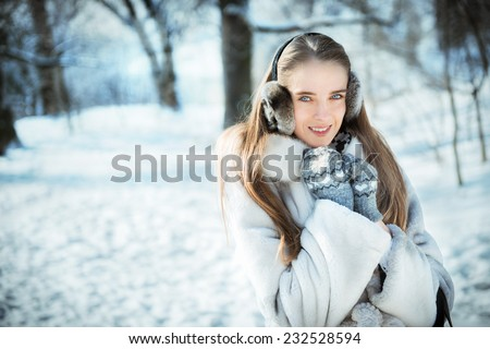 Happy beautiful woman walking in earmuff, knitted mittens and fur coat have fun in winter forest - stock photo