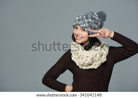 Happy beautiful woman wearing warm winter clothing pulling a hand gesture peace sign in front of her face, over grey background - stock photo