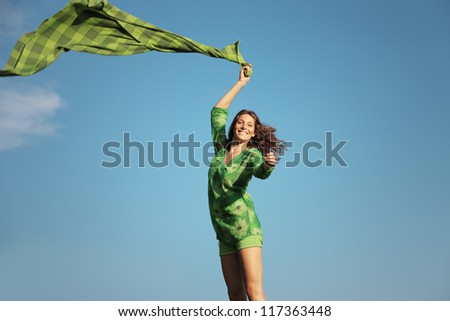 Happy beautiful  woman with a green tissue against blue sky