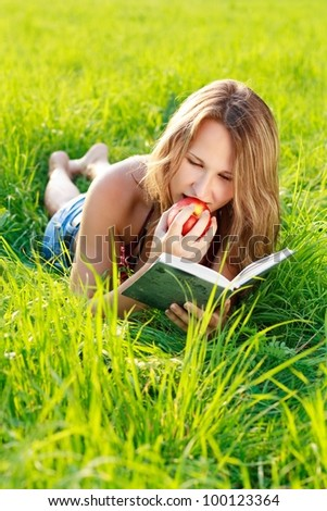 Happy beautiful woman with an apple in hand lying on the green grass and reading a book a sunny day against a background of green nature