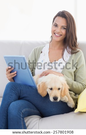 Happy beautiful woman with dog using tablet computer on sofa at home - stock photo