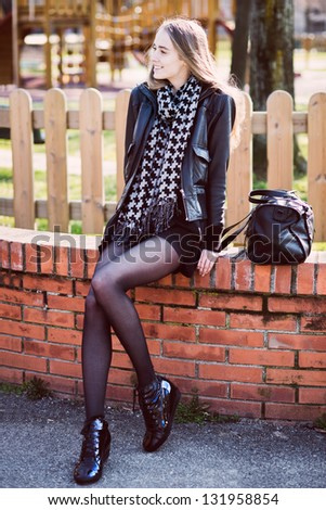 Happy beautiful woman with long legs sitting in the park - stock photo