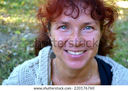 Happy beautiful woman with red hair in her fourties smilling outdoors - stock photo