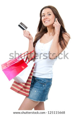 Happy Beautiful woman with shopping bags and credit gift card talking on cellular mobile phone, cheerful smiling on a white background - stock photo