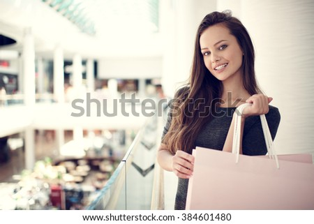 Happy beautiful woman with shopping bags stands at shop. Attractive caucasian girl with purchasing bags in big mall - stock photo