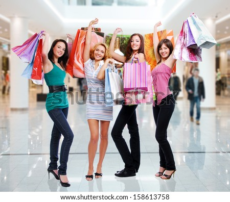 Happy beautiful women with shopping bags stands at shop