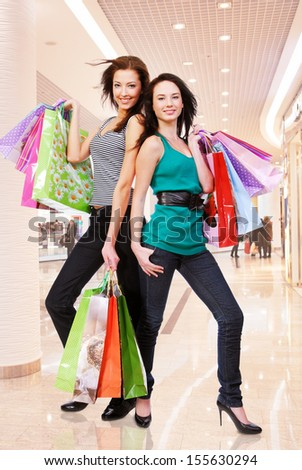 Happy beautiful Young adult girls with shopping bags at shop - stock photo