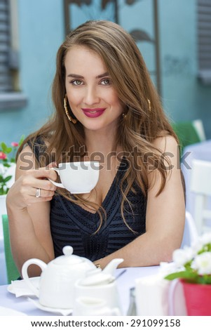 Happy Beautiful young blonde woman sitting in a coffee shop and drink tea - stock photo
