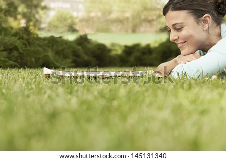 Happy beautiful young businesswoman reading newspaper while lying on grass at park - stock photo