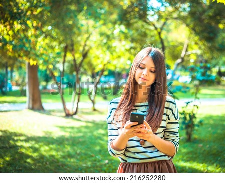 Happy beautiful young Caucasian girl with smart phone outdoors on sunny summer day tex-ting and smiling.  - stock photo