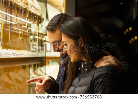 Happy beautiful young couple choosing a wedding rings while smiling while doing shopping in Florence.