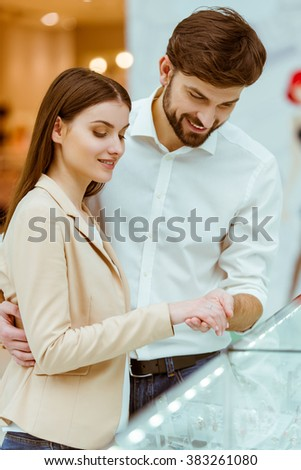 Happy beautiful young couple trying a wedding ring on and smiling while doing shopping in mall - stock photo