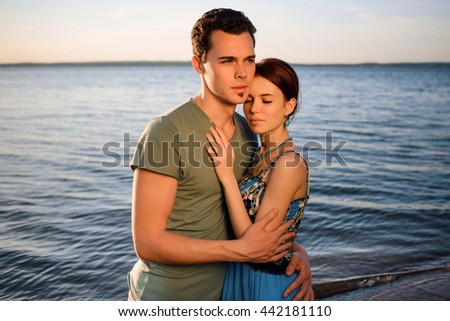 Happy beautiful young couple walking and embracing on the beach of the sea at summer sunset. Concept of the love and family, summer holiday, vacation, travel.