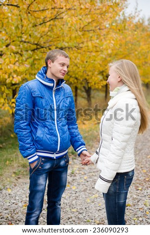 Happy beautiful young couple walking outdoors on cold autumn day